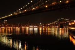 New York City at Night. Along a new york city river at night around brooklyn bridges with lights stock photos