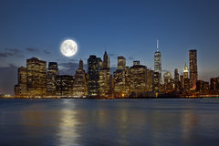 New York City at night. Panoramic view New York City Manhattan downtown skyline at night with skyscrapers and bright full moon royalty free stock photos
