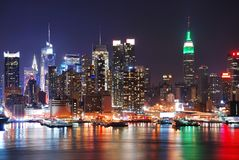 New York City night skyline. Over Hudson river with boat and skyscraper and colorful reflections stock images