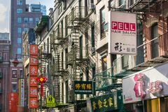 New York City, NY/los E.E.U.U. - 08/01/2018: Muestras del negocio a lo largo de una calle encogida en el área de Chinatown de New imagen de archivo