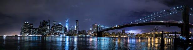 New York City NY/USA - circa Juli 2015: Panorama av den Brooklyn bron och Lower Manhattan vid natt arkivfoto