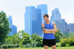 New York City runner listening music on smartphone. New York City man runner listening music on smartphone. Male adult jogger running using touchscreen on Royalty Free Stock Photos