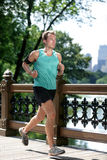 New York City runner running listening to music. With smartphone armband. Athletic young man exercising cardio using mobile phone app and earphones for workout Stock Photography