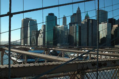 New York City Skyline USA. Financial District of Manhattan, New York City, framed in the forground by the cables and structure of the Brooklyn Bridge stock images