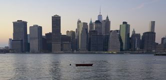 New York City Skyline, boat. A small dingy sits in the river with the New York City Skyline in the background Stock Photo