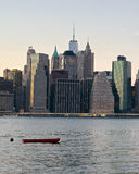 New York City, Boat. A lone boat sits along with New York City skyline  background. Isolated red boat or dingy Royalty Free Stock Images