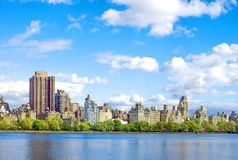 New York City skyline, NY. Skyline of New York City over Central Park lake in New York, USA with blue skies royalty free stock photo