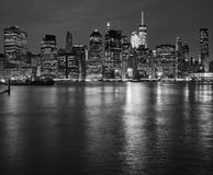 New York City skyline reflected in East River at night, USA. Stock Photos