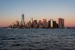 New York city skyline sunset view from the boat to Ellis Island royalty free stock photography