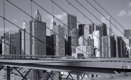 New York City skyscrapers seen through the wires of the Brooklyn Bridge. Stock Image