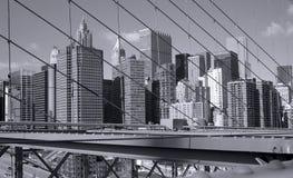 New York City skyskrapor som ses till och med trådarna av den Brooklyn bron Fotografering för Bildbyråer