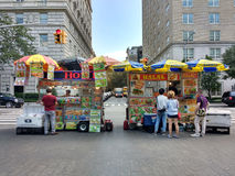 New York City Street Food Vendors on 5th Avenue, Near the Metropolitan Museum of Art, the Met, Manhattan, NYC, NY, USA. People stand in front of two food carts Royalty Free Stock Images