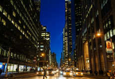 New York city street at night. With a pedestrian on a crosswalk in front of yellow taxi cabs Stock Photo