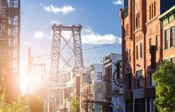 New York City street scene with sunlight shining on the Williams. Burg Bridge in Brooklyn NYC Stock Photos