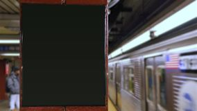 Manhattan Subway Train Approaches Underground Platform with Blank ID Sign. A New York City subway car approaches an underground platform with a blank ID sign for stock footage