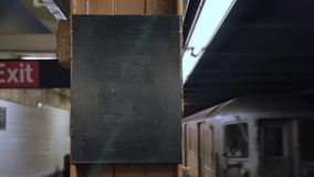 New York City Subway Train Approaches Platform with Blank ID Sign. A Manhattan subway car arrives at a station. With audio and blank sign on pillar for stock footage