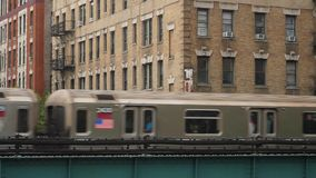 Elevated Subway Train Passes Harlem Apartment Buildings and Liquor Store. 9412 A New York City subway train passes by Harlem apartment buildings and a corner stock video