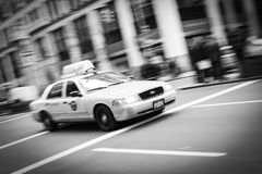 New York City Taxi Blur Black and White. A New York City taxi drives down a busy street in New York. Panning was used along with a zoom lens technique to capture Stock Photos