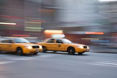 New York City Taxi zooming past. Two Yellow cabs in New York City zooming past on a street in Manhattan Stock Images