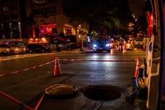 New York City, 46th rua do leste, Manhattan - 1º de novembro de 2017: Uma tampa de câmara de visita é obstruída fora com os fios  Imagens de Stock Royalty Free
