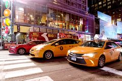 Yellow taxis and tourism bus in midtown at night Manhattan New York. New York City, USA - April 2018: Yellow taxis and tourism bus in midtown at night Stock Photos