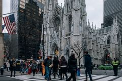 St. Patrick`s Cathedral street scene in the Midtown Manhattan. Towering Neo-Gothic church from 1879 with twin spires & storied stock image