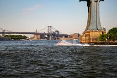 New York, City / USA - JUL 10 2018: Man wearing clown suite riding jet ski water bike in East River under Manhattan Bridge royalty free stock image