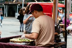 Brooklyn Flea Market in DUMBO in New York. New York City, USA - June 24, 2018: Man preparing fresh food in Brooklyn Flea Market in DUMBO. It includes vendors of royalty free stock photos