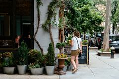 Picturesque street view in Greenwich Village, New York. New York City, USA - June 22, 2018: Woman at fashionable restaurant in the corner of Gay Street with Stock Image