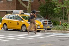 The American woman crosses the pedestrian crossing while the tax. New York City, USA - June 08, 2017: New York yellow taxi cab stop at pedestrians traffic lights Royalty Free Stock Image