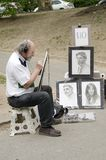 Artist draftsman drawing portraits in Central Park in NYC. New York City, USA - May 05, 2015: an artist draftsman drawing portraits in Central Park in Manhattan royalty free stock images