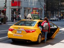 Woman taking taxi on fifth avenue in Manhattan. New York City, USA - May 2018: Woman taking taxi on fifth avenue in Manhattan Stock Image