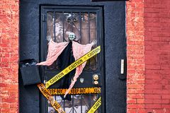 Halloween decorations including a witch and decorative police stripes on the front door of a house in Brooklyn, New York royalty free stock photos
