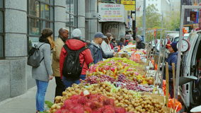 New York City, USA - OKTOBER, 2016: Passers buy fruits and vegetables in Chinatown New York. Chinatown in Manhattan, New York. Street vendors sell fruits and stock footage