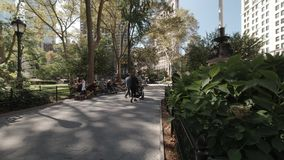 People relaxing and walking in Madison Square Park in Flatiron District Midtown Manhattan