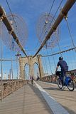 Cycling on Brooklyn bridge. NEW YORK CITY, USA, September 11, 2017 : Brooklyn Bridge. The Brooklyn Bridge is a hybrid cable-stayed suspension bridge and is one Royalty Free Stock Photo