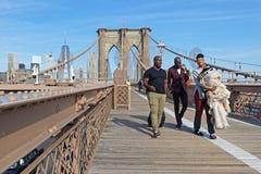 Three people crossing Brooklyn Bridge. NEW YORK CITY, USA, September 11, 2017 : Brooklyn Bridge. The Brooklyn Bridge is a hybrid cable-stayed suspension bridge Stock Photo
