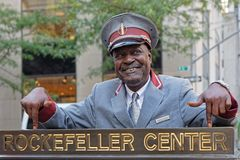 Welcoming the tourists at the center. NEW YORK CITY, USA, September 11, 2017 : Man in uniform welcomes tourists for the Rockfeller center visit Stock Images