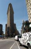 New York City USA: Strykjärnbyggnad och skåpbilar med grafitti Arkivfoton