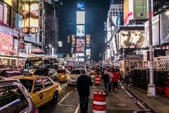 New York City - Vereinigte Staaten - 25 05 2014 - Times Square-Nachtmenschen, die um das Auto-Taxifahren gehen Stockfotos