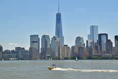 New York City Viewed from Liberty State Park across Hudson River. With a yellow boat crossing in speed and Freedom Tower being the tallest building royalty free stock images