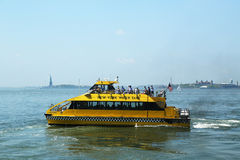 New York City Water Taxi in the front of Statue of Liberty and Ellis Island Stock Photography