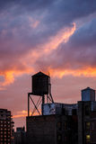 New York City water tower at sunset. Sunset golden light enhancing the fiery colors of the clouds in NYC sky and outlining Chelsea building tops and a water Royalty Free Stock Image