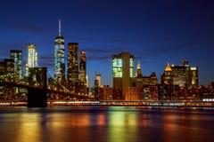 New York City & x27; upplyst bro- och Manhattan för s Brooklyn horisont Arkivbilder