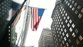 NEW YORK, DE V.S. - DECEMBER, 2017: Wolkenkrabbers in mist, mening van bodem, Amerikaanse vlag op het gebouw stock video