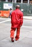 NEW YORK, de V.S. - 15 JUNI, 2015 - Rode geklede zwarte mens die in Harlem op weekdag lopen Stock Afbeeldingen