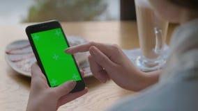 New York, de V.S. - 9 Mei, 2019: Aantrekkelijke jonge vrouw die haar groene telefoon van de touch screen mobiele cel in koffie me stock videobeelden