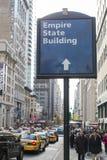 NEW YORK, DEGLI STATI UNITI 23 NOVEMBRE: Insegna della via con il segnale di direzione a Fotografia Stock Libera da Diritti