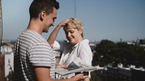 New York, em julho de 2018 Homem novo e mulher que estão junto com os jornais, apreciando a fala no balcão ensolarado pequeno vídeos de arquivo