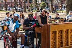 NEW YORK, ETATS-UNIS - 14 AVRIL 2018 : Hommes presque chantant et jouant le piano en parc avec le village occidental, New York photo libre de droits